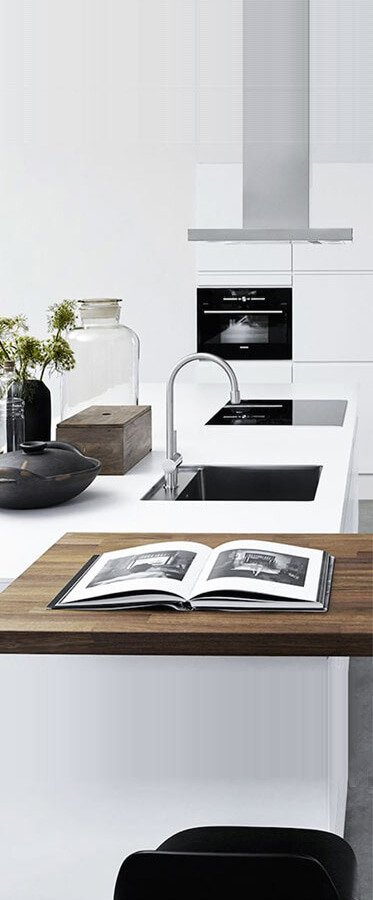 ultra modern kitchen featuring quartz counter glass stove and folk craft kitchen accessories
