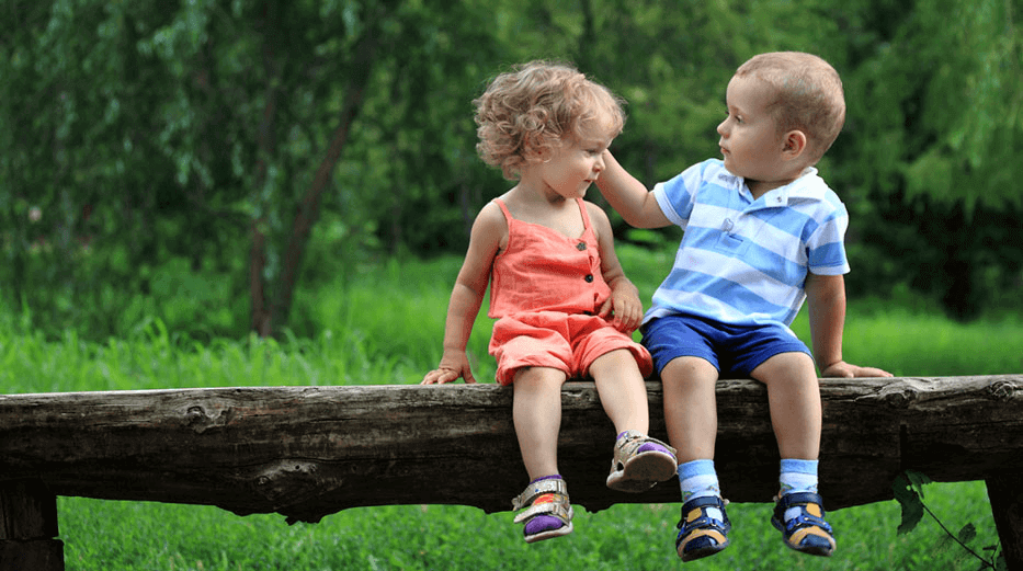 Two toddlers sit on a log bench, the boy gently brushing back the girl's curly hair with his hand.