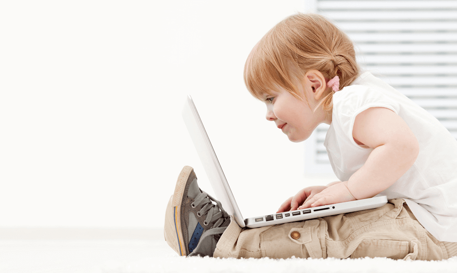 a young girl intently studies the screen of a laptop