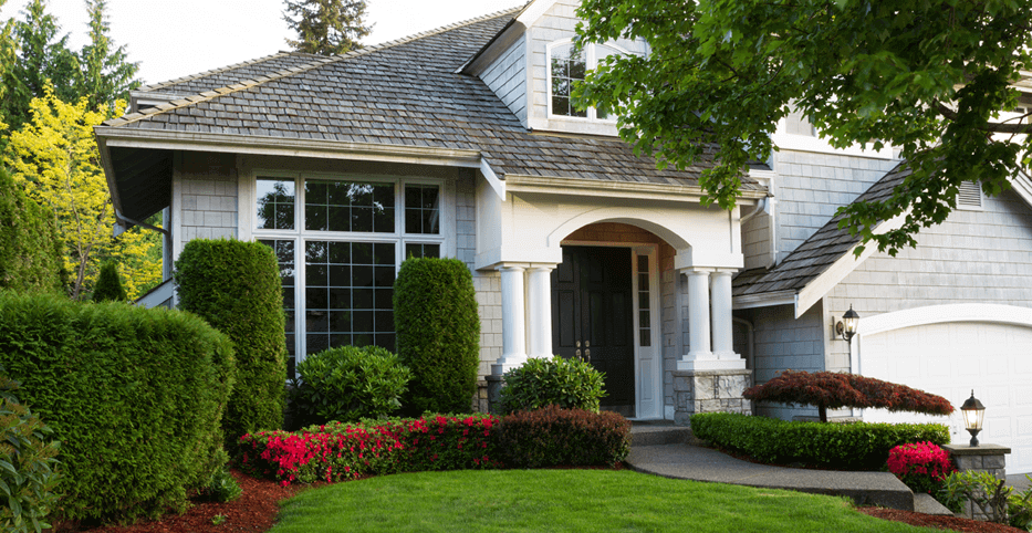 the front entrance to a traditional upscale home with pristine landscaping