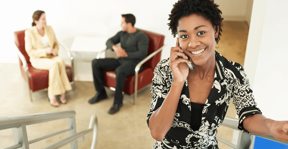 businesswoman negotiates on her phone while two clients patiently wait in the background