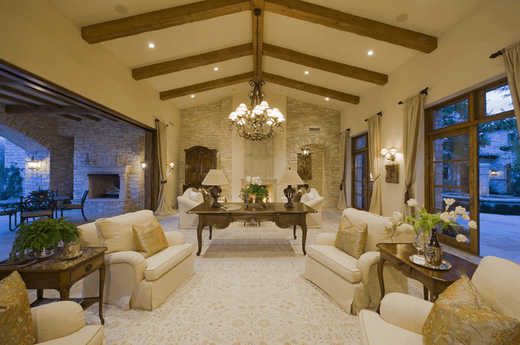 Elegant plein-air living room with vaulted ceiling and gold accents