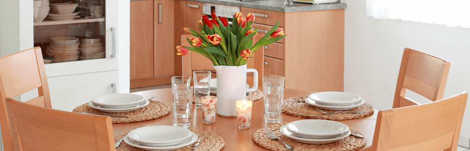 a de-cluttered kitchen table setting with a bouquet of tulips artistically displayed in a pitcher