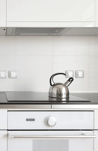 a stainless teakettle rests on a glass stovetop in a pristine contemporary kitchen