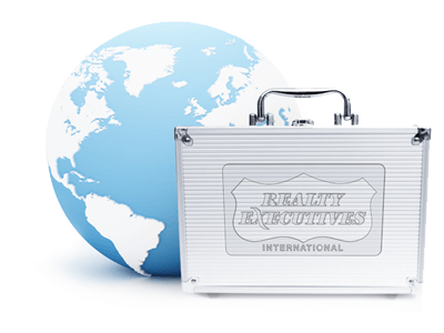 the Realty Executives logo embossed on a metal briefcase with a model globe in the background