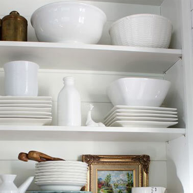 close-up of open shelves storing sleek dinnerware and serving bowls