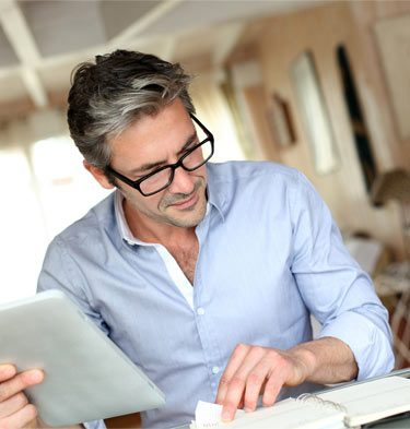 middle-aged relaxed man reviewing business documents in his home office