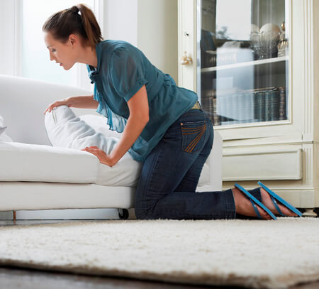 Young woman searches for something under a sofa cushion