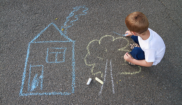 Boy drawing house and tree with chalk