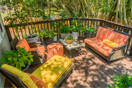 Backyard patio set with bright orange striped cushions and a yellow chaise lounge