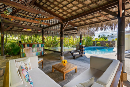 tropically decorated backyard patio with grass roof