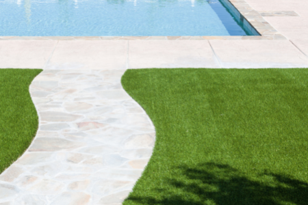 stone path to a pool surrounded by artificial grass