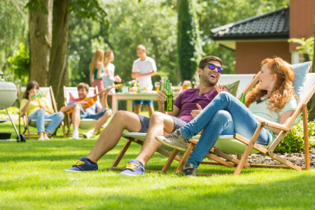 Man and woman sitting on folding lawn chairs in green grass