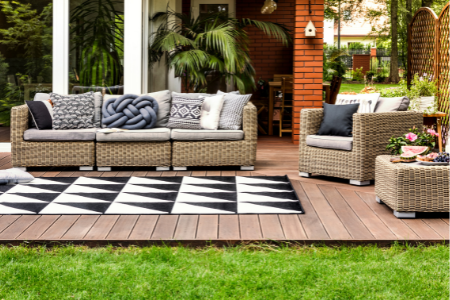 backyard wooden deck with couch, chair, and gray patterned fabric