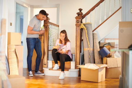 Two young adults considering their personal belongings when choosing a home insurance plan.
