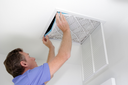man replacing an air filter to reduce HVAC energy costs