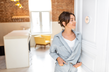 A woman looking at the smart thermostat she installed to save money on her energy bill.