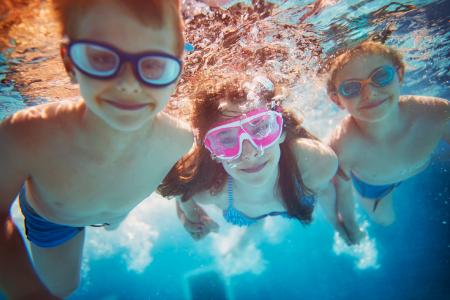 3 children swimming underwater in the pool