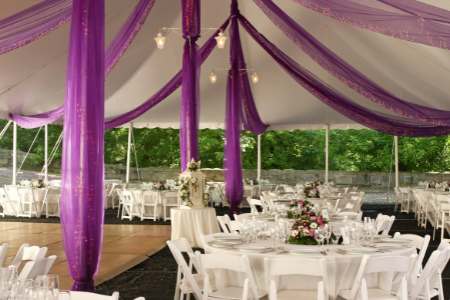 Purple sashes hang from the ceiling of a white tent set up for a backyard wedding.