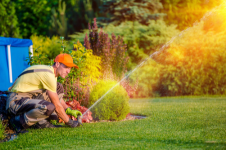 A man adjusts sprinklers to care for a lawn.