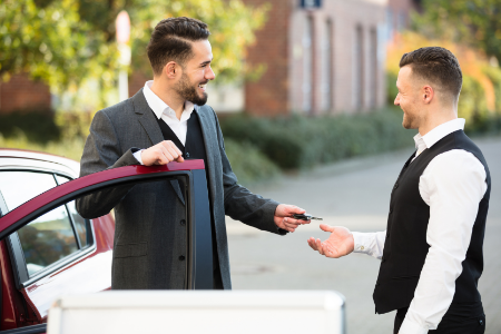 A man hands the valet the keys to his car.