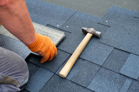 Man placing a new shingle on a roof as part of a common major home repair.