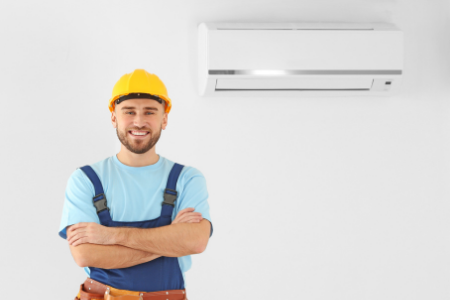 Repair person with an air conditioner, one of the appliances commonly covered with a home warranty.