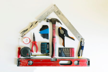 Multiple tools shaped as a home to symbolize home repairs