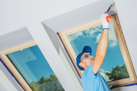 Man painting a high ceiling with two windows.
