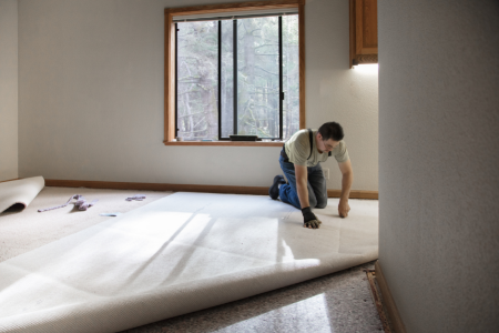 A man laying carpet in a room.