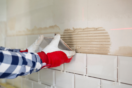 A professional tackling the complicated home improvement project of laying a tile backsplash.