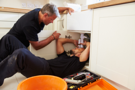 A professional plumber tackling a leak under the sink.
