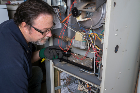 A man inspecting a furnace.