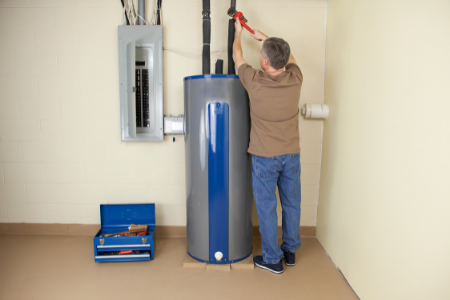 Man checking his hot water heater to see if it needs repair or replacement.