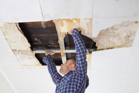 Man checking a leak in the ceiling that has caused water damage, a common major home repair.