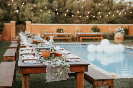Backyard wedding with long dinner table set up near the pool.
