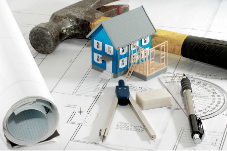 home improvement project planning with a hammer, protractor, and small house over floorplans