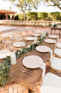 table set with white plates and green leaves for decoration.