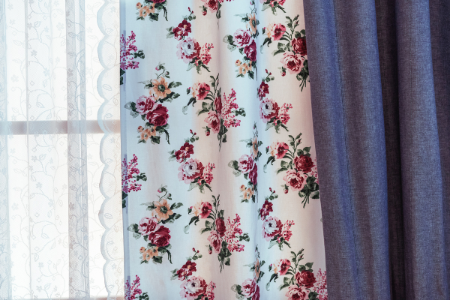 a granny chic design trend of layering a lace curtain with a floral and denim curtain