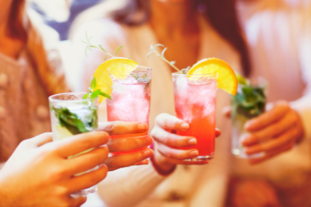 Three ladies toasting with their cocktails for the end of summer.