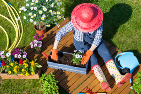 A woman potting plants in her small garden space.