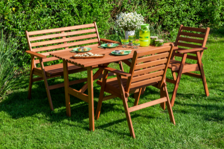 A garden set with a folding table, bench, and two chairs.