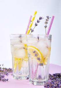 Lavender lemonade mocktail garnished with lavender sprigs and colorful straws.