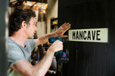 A man hanging a mancave sign on the door.