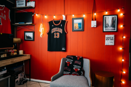 A Chicago Bulls themed man cave with jerseys and framed photos as decor.