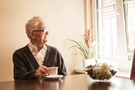 An older man looking out the window of his home that includes the features senior buyers should look for.