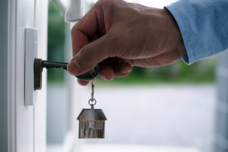 a key going into a door, symbolizing homeownership