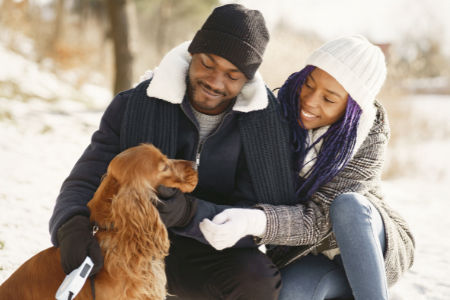 A man and woman checking to make sure their pet is safe in the colder climate.
